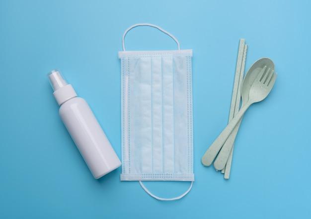Acessório pessoal com máscara facial desinfetante de mãos branco ou gel de álcool e conjunto de colher verde proteção contra coronavírus em fundos azuis