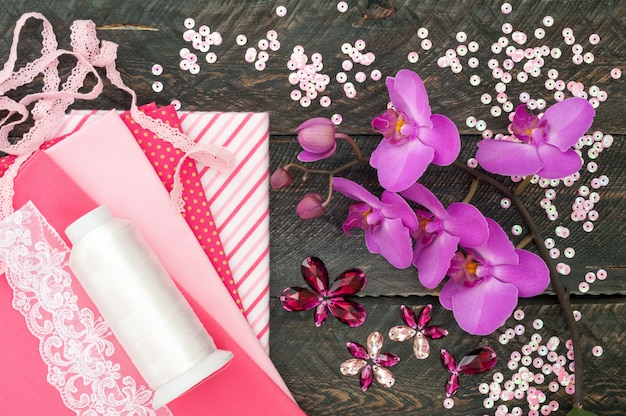 Acessórios artesanais. tecido de algodão, renda, linha da bobina, cristais e lantejoulas para bordar em fundo de madeira velho. flores da orquídea