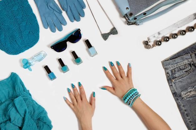 Acessórios azuis da moda, cosméticos decorativos e outros itens elegantes em um fundo branco.