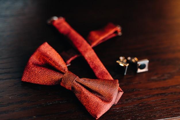 Acessórios classic groom: gravata borboleta vermelha e abotoaduras na mesa. manhã do noivo.