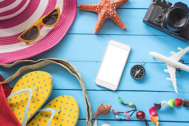 Acessórios com mulher para o verão de viagens. no chão de madeira azul
