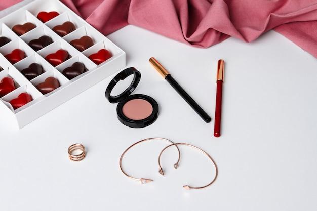 Acessórios cosméticos decorativos e chocolate sobre a superfície branca