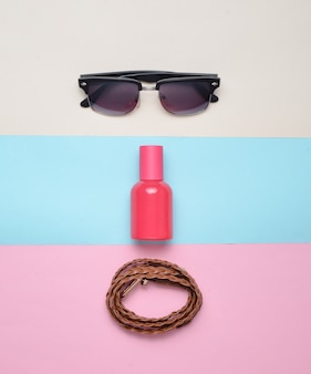 Acessórios da moda feminina em um fundo pastel multicolorido. óculos, perfume, cinto de couro. vista do topo. minimalismo.
