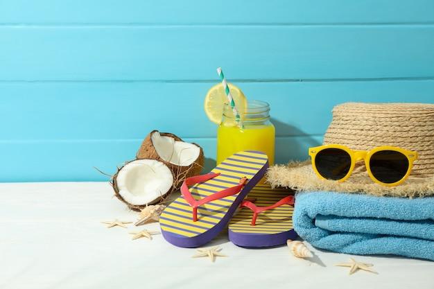 Acessórios das férias de verão na tabela branca contra o fundo de madeira da cor, espaço para o texto. boas festas