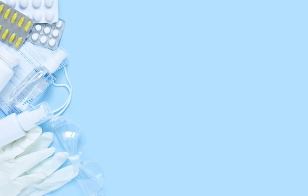 Acessórios de antivírus: anti-séptico, máscara, luvas e comprimidos em fundo azul.flatly.pandemic.