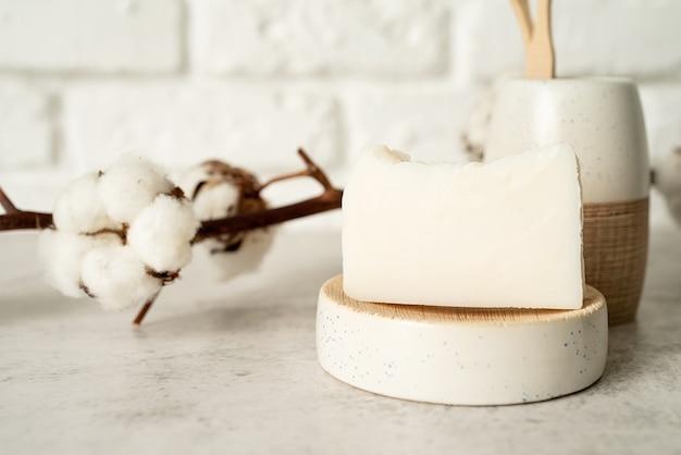 Acessórios de banho com escovas de bambu e sabonete artesanal na prateleira da banheira, vista frontal