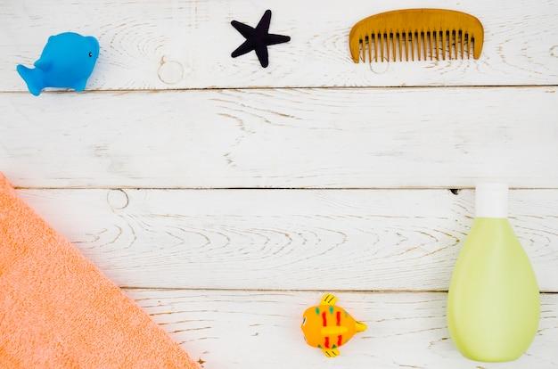 Acessórios de banho de bebê vista superior com fundo de madeira