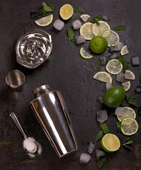 Acessórios de bar e ingredientes para coquetéis de lima, menta, gelo.