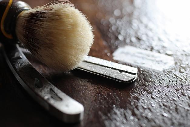 Acessórios de barbear em fundo de textura de madeira e lâminas descartáveis