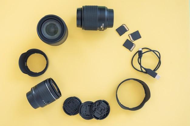 Acessórios de câmera digital profissional dispostos em círculo sobre fundo amarelo