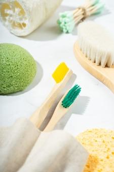 Acessórios de casa de banho ecológicos naturais: pente de madeira, escova de dentes de bambu, escova de massagem, palitos para as orelhas, esponja konjac sobre fundo de mármore. desperdício zero de produtos éticos. close up, flat lay, top view