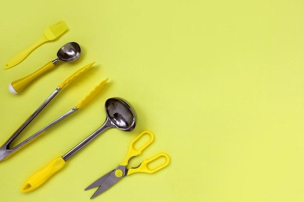 Acessórios de concha de cozinha, tesoura, tenaz, escova, colher de sorvete amarelo sobre um fundo amarelo