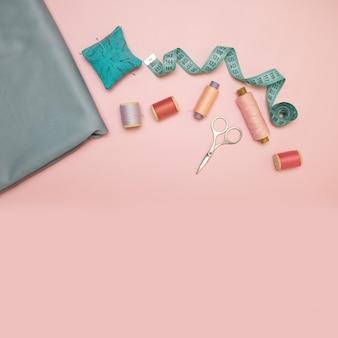 Acessórios de costura e tecido em um fundo rosa.