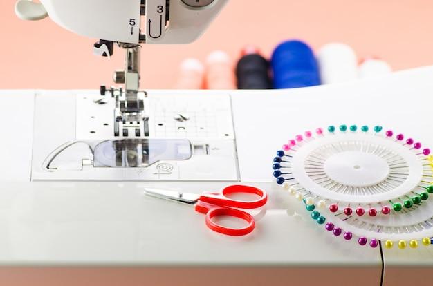 Acessórios de costura estão em uma máquina de costura branca: tesoura e agulhas inglesas