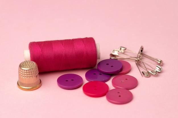 Acessórios de costura, incluindo carretéis de linha e alfinetes na superfície rosa