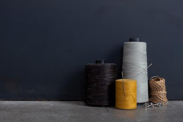 Acessórios de costura. tesoura, agulha, dedal em fundo preto