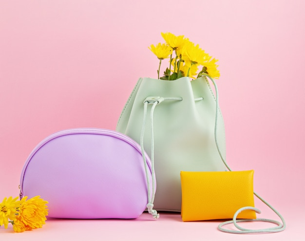 Acessórios de couro para meninas em tons pastel brilhantes: mão ruim, bolsa, bolsa de maquiagem e flores sobre fundo rosa