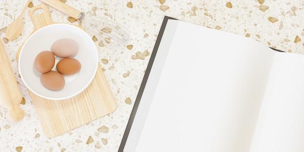 Acessórios de cozinha de madeira para fazer bolos com um grande livro em branco ao lado e ovos dentro de uma tigela