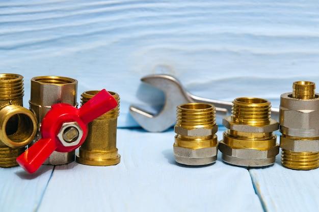 Acessórios de encanamento e chave ajustável em placas de madeira azuis durante o reparo ou substituição de peças sobressalentes