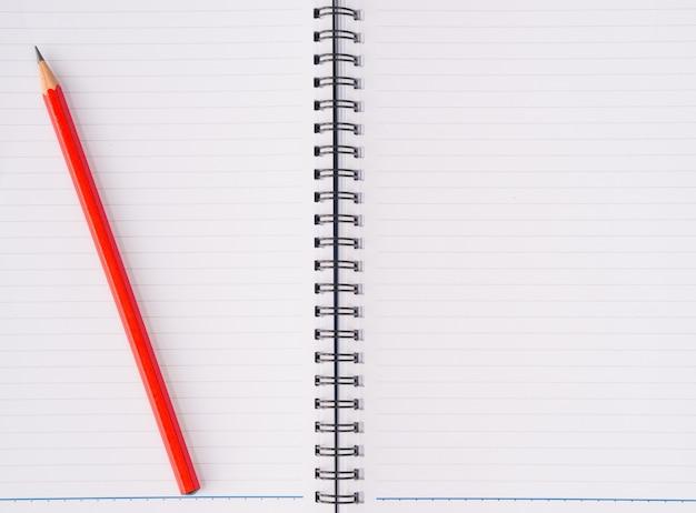 Acessórios de escritório, incluindo caderno e lápis vermelho.