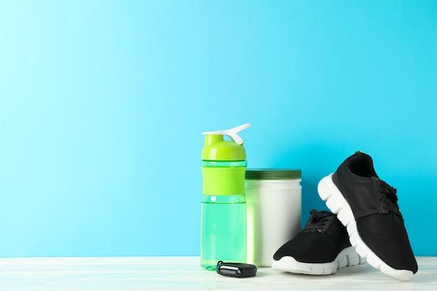 Acessórios de estilo de vida esportivo na mesa de madeira branca contra o fundo azul