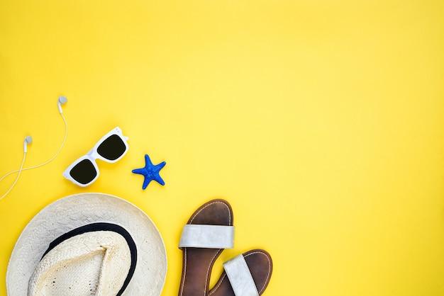 Acessórios de férias de verão. chapéu de palha, óculos de sol brancos, fones de ouvido e flip-flops sobre fundo amarelo. copie o espaço, plana leigos.