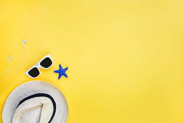 Acessórios de férias de verão. chapéu de palha, óculos de sol brancos, fones de ouvido e smartphone sobre fundo amarelo. copie o espaço, lay plana, mock-up.