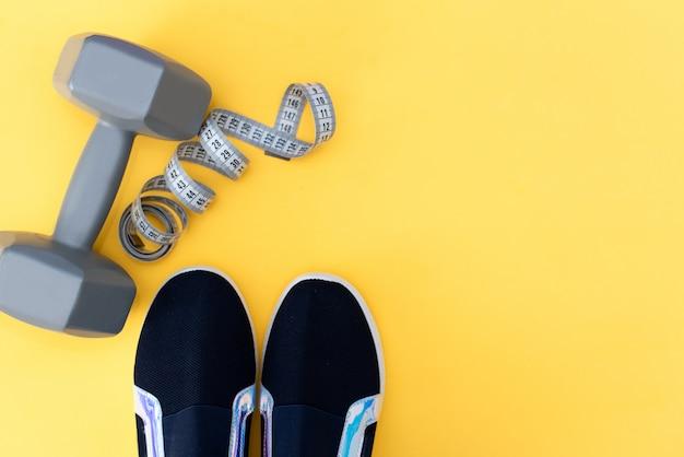 Acessórios de fitness em um fundo amarelo. tênis, garrafa de água, fones de ouvido e halteres.