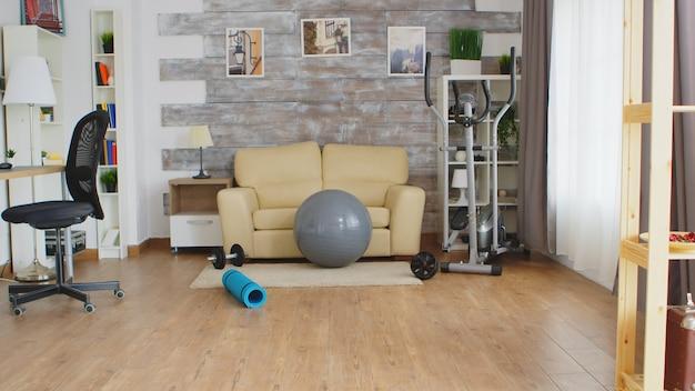 Acessórios de fitness para treino em casa numa sala sem ninguém dentro.