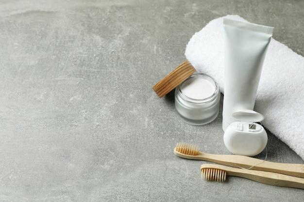 Acessórios de higiene bucal em fundo cinza texturizado