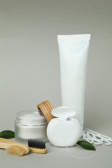 Acessórios de higiene bucal em fundo cinza, tubo em branco