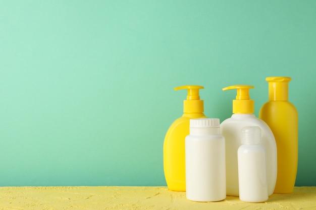 Acessórios de higiene do bebê na mesa amarela contra a parede de hortelã