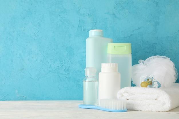 Acessórios de higiene do bebê na mesa de madeira contra a parede azul