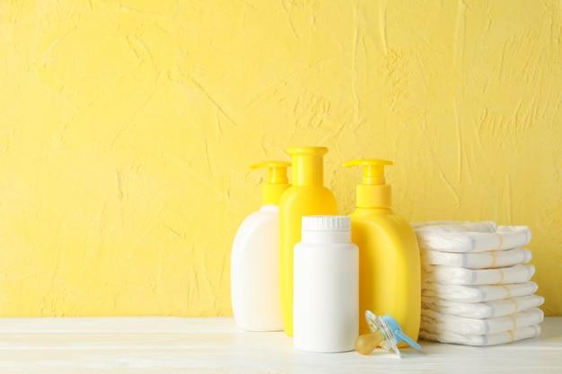 Acessórios de higiene do bebê na mesa de madeira contra parede amarela