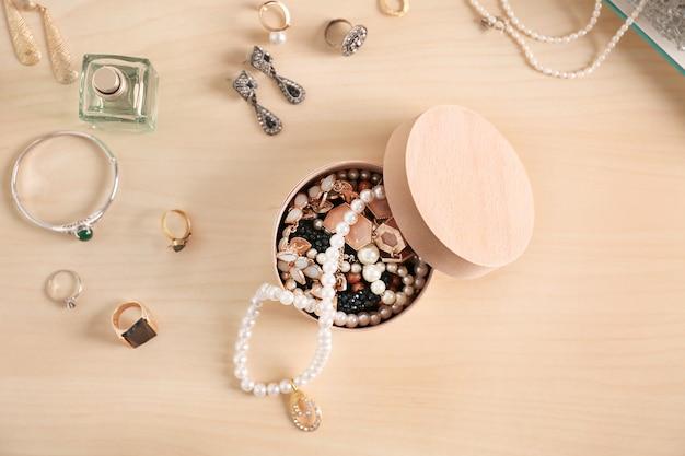 Acessórios de joalheria em caixa e mesa, vista de cima