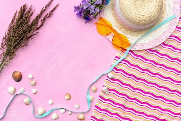 Acessórios de lazer de verão em um fundo rosa com conchas.