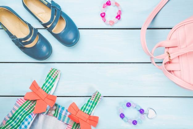 Acessórios de menina. bolsa rosa com vestido colorido, argola, laços de cabelo e sapatos na superfície de madeira pastel azul.