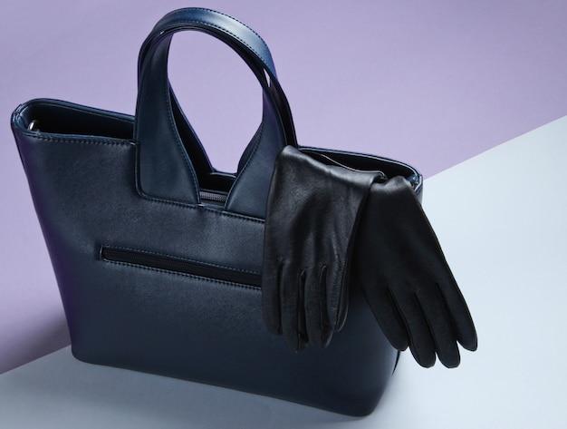 Acessórios de moda feminina em fundo cinza-roxo. bolsa de couro, luvas.