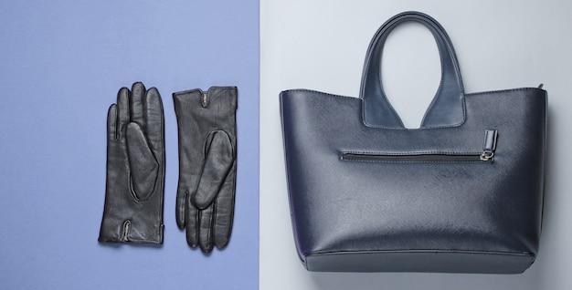 Acessórios de moda feminina em um fundo cinza-roxo. bolsa de couro, luvas. vista do topo