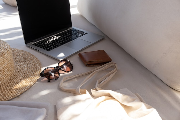 Acessórios de moda feminina. óculos de sol femininos elegantes, chapéu de palha, bolsa de compras, laptop no sofá branco com almofadas