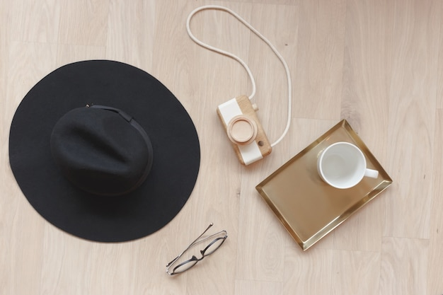 Acessórios de moda plana leigos em estilo retro. composição estilo vintage com câmera de madeira, óculos, chapéu e xícara