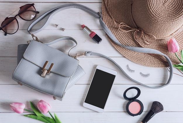 Acessórios de mulher com maquiagem, cosméticos, escova e telefone inteligente