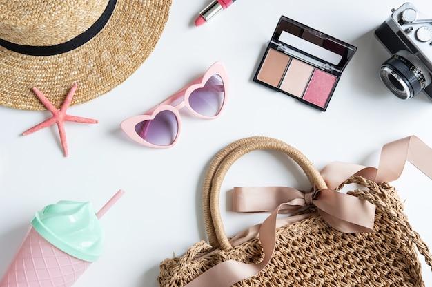 Acessórios de mulher e viagem com maquiagem, cosméticos, pincel e câmera, vista superior