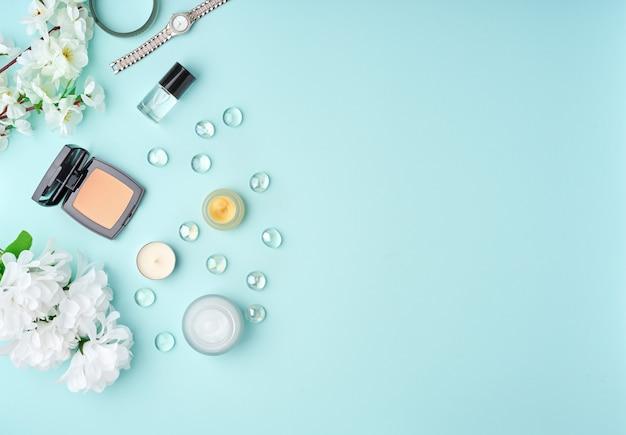 Acessórios de mulher plana leigos com cosméticos, creme facial, saco, flores na mesa azul pastel