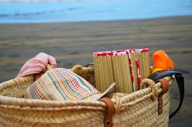 Acessórios de natação no litoral para o conceito de verão ou férias. bolsa de praia, chapéu de sol, óculos e biquíni na praia.