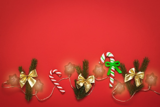 Acessórios de natal com festão em um fundo vermelho brilhante.