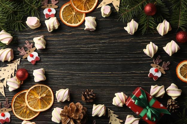 Acessórios de natal e marshmallow em fundo de madeira