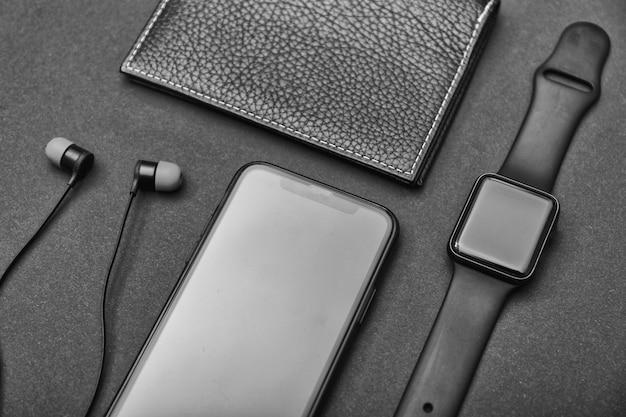 Acessórios de negócios masculinos fones de ouvido, relógio, carteiras e um celular em uma mesa preta