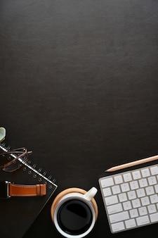 Acessórios de negócios na parte superior da mesa de couro escuro e espaço de cópia