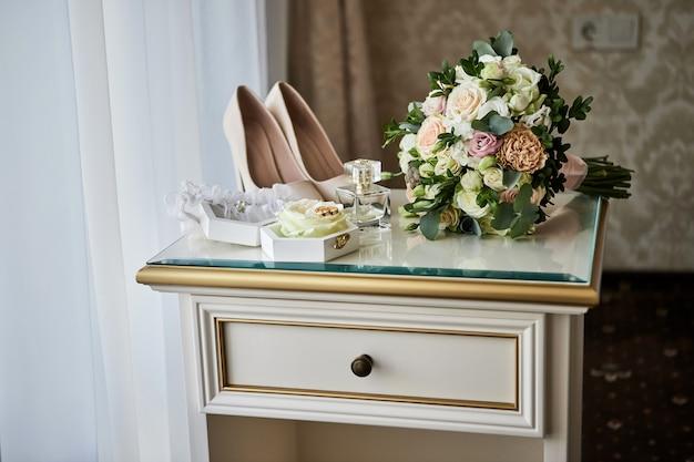 Acessórios de noiva como sapatos, buquê, anel e perfume em uma mesa